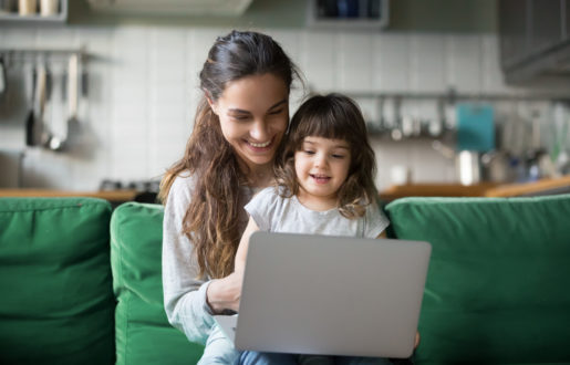 Happy laughing single mother and little preschool cute daughter using laptop online application, making video call, having fun, babysitter teaching small girl use computer, watching cartoons together